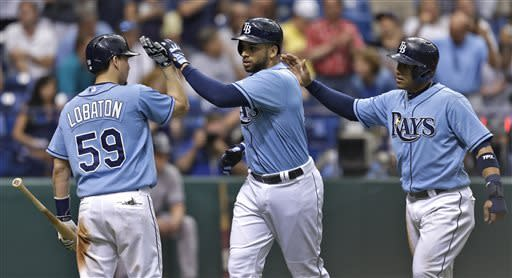 Tampa Bay Rays' James Loney, center, and Yunel Escobar, right, high five on-deck batter Jose Lobaton after Loney hit a sixth-inning, two-run home run off New York Yankees starting pitcher CC Sabathia during the MLB American League baseball game Sunday, May 26, 2013, in St. Petersburg, Fla. Escobar also scored on the home run. (AP Photo/Chris O'Meara)