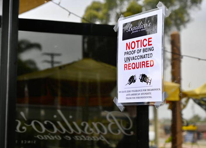 """A sign taped to the window of California restaurant Basilicos Pasta e vino says they require """"proof of being unvaccinated."""""""