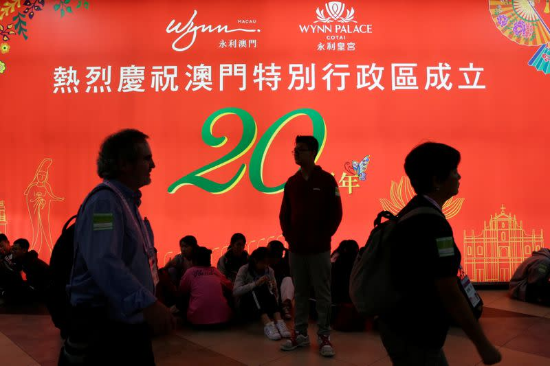 People walk past a Wynn Resorts sign celebrating 20 years since the establishment of Macau Special Administrative Region, at Macau International Airport in Macau