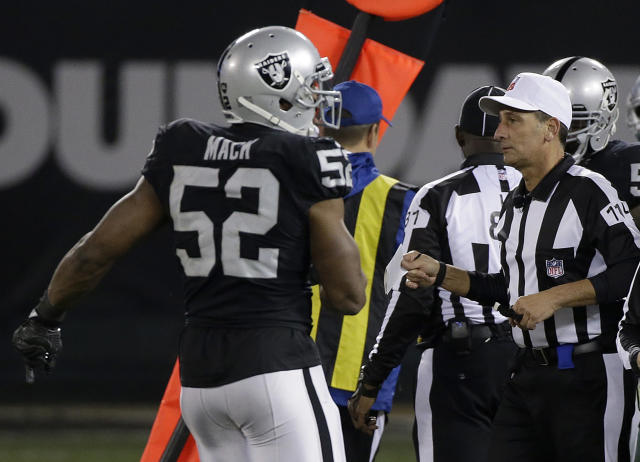 NFL referee Gene Steratore, right, whose use of an index card to help determine a first down in a Raiders-Cowboys game last December drew strong reaction, is retiring. (AP)
