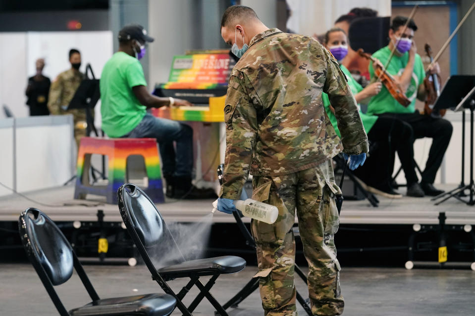 A member of the New York National Guard sprays a chair with disinfectant between arrivals of groups waiting during the post-vaccination observation period Tuesday, March 23, 2021, in New York, at the Jacob K. Javits Convention Center vaccination site. (AP Photo/Kathy Willens)