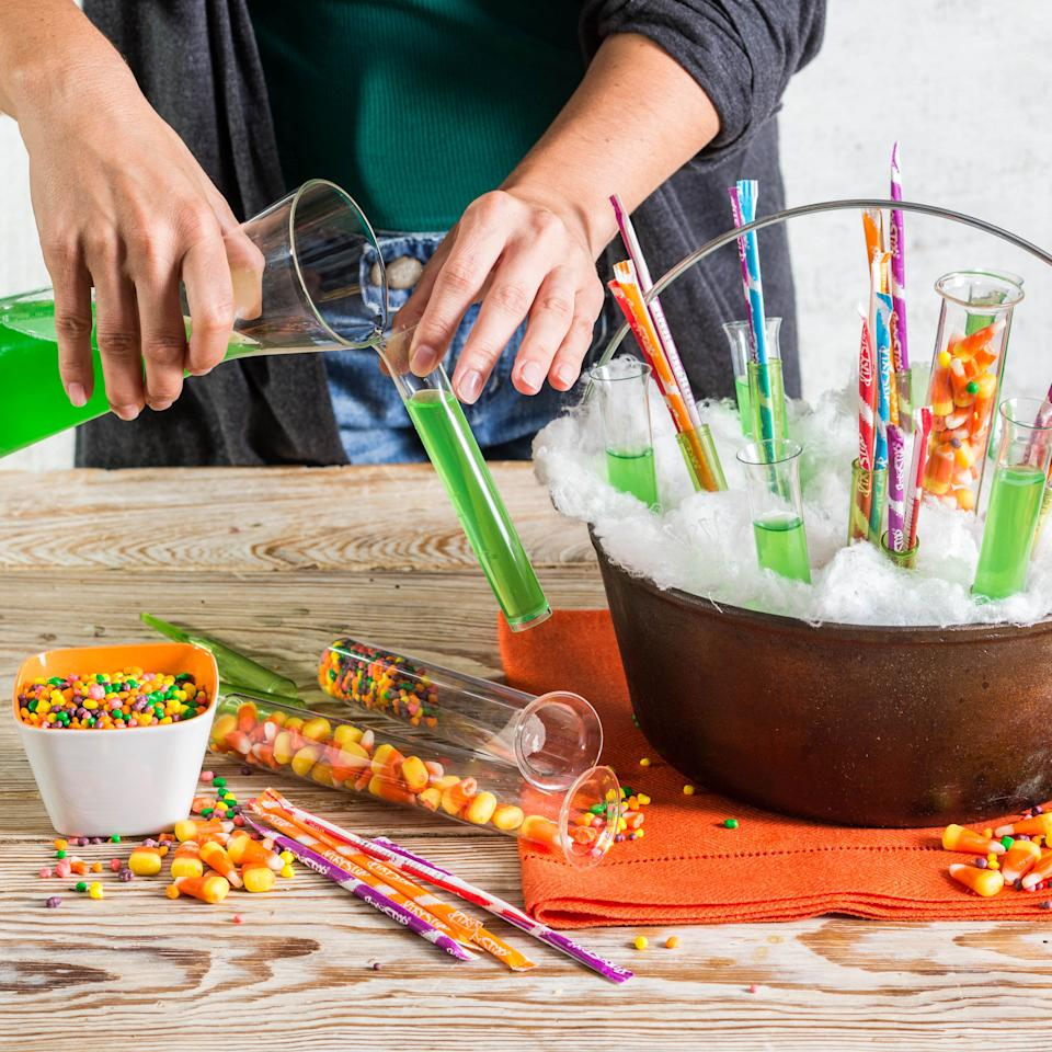 "<p>Insert florist picks and plastic ""test tubes"" randomly into foam. Fill florist picks with stick-type candy. Fill some tubes with various candy pieces and fill other tubes with green juice.</p>"