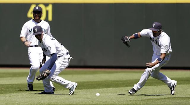 Seattle Mariners right fielder Endy Chavez, right, races to the ball from Minnesota Twins' Chris Colabello that fell between center fielder Dustin Ackley, left, and second baseman Nick Franklin in the fourth inning of a baseball game, Saturday, July 27, 2013, in Seattle. (AP Photo/Elaine Thompson)