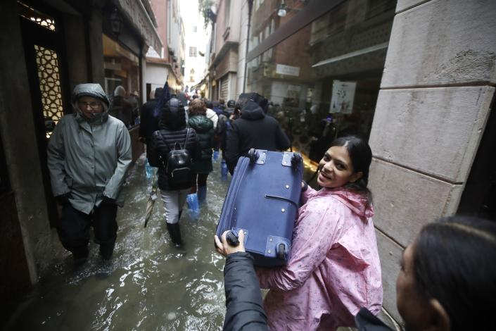 Tourists carry their luggage as they wade through water on the occasion of a high tide, in a flooded Venice, Italy, Tuesday, Nov. 12, 2019. (Photo: Luca Bruno/AP)