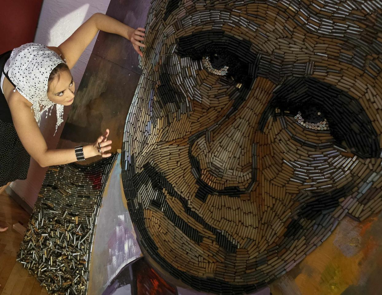 "Ukrainian artist Dariya Marchenko works on a portrait of Russian President Vladimir Putin named ""The Face of War"" which is made out of 5,000 cartridges brought from the frontline in eastern Ukraine, in Kiev, July 23, 2015. The portrait will be presented along with a novel which will tell personal stories of six people involved in this project including Daria's own story and stories of people who helped her to collect shells from the frontline. Daria Marchenko calls her art approach philosophic symbolism where every element has its hidden meaning. In her works cartridges mean human's life that was brutally ended. Picture taken July 23, 2015. REUTERS/Gleb Garanich TPX IMAGES OF THE DAY"