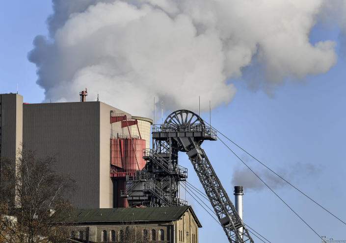 A coal-fired power station steams behind the pit frame of Germany's next to last coal mine in Ibbenbueren, Germany, Tuesday, Dec. 4, 2018. An industrial history will end later this month when the last stone coal mine in Germany will be closed in Bottrop. (AP Photo/Martin Meissner)
