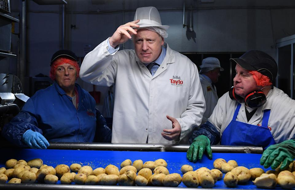 Boris Johnson helps quality control staff during a general election campaign visit to the Tayto Castle crisp factory in County Armagh, Northern Ireland, in 2019 (Photo: DANIEL LEAL-OLIVAS via Getty Images)