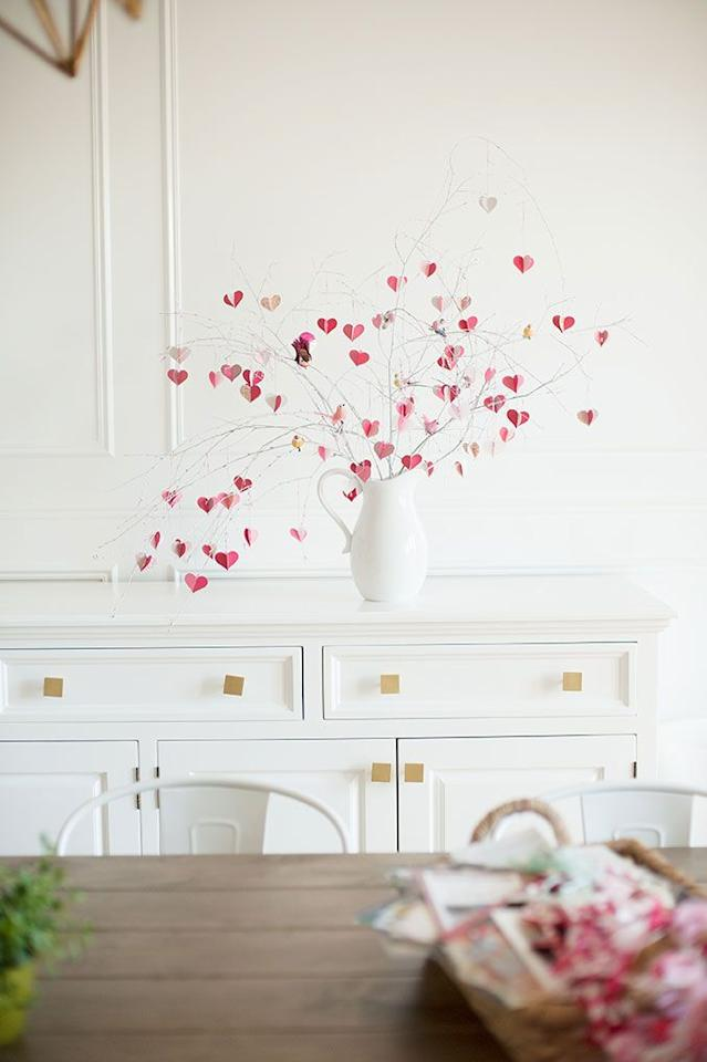 """<p>Make love grow on trees with this simple craft that requires little more than a few cutout hearts and tree branches that are spray-painted white.</p><p><em><a href=""""https://thehousethatlarsbuilt.com/2015/01/diy-valentines-day-branch-tree.html/"""" target=""""_blank"""">Get the tutorial at The House That Lars Built »</a></em></p>"""