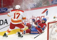 Montreal Canadiens' Phillip Danault falls after taking a hit from Calgary Flames' Milan Lucic during the first period of an NHL hockey game Friday, April 16, 2021, in Montreal. (Paul Chiasson/The Canadian Press via AP)