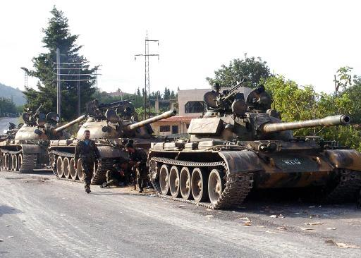 Syrian army tanks parked on the side of a road during an alleged pursuit of opposition fighters in the Latakia province on August 8, 2013