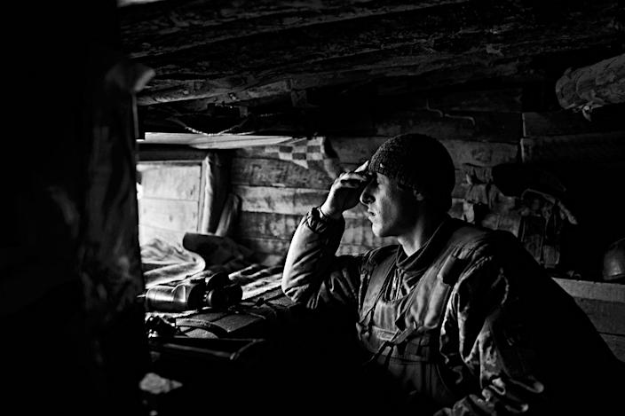<p>An exhausted Ukrainian soldier reacts while observing enemy positions from a makeshift bunker at a position in a frontline around the village of Novotroitska, at the Mariupol sector in Donbas Oblast in Ukraine, in April 2017. (Photo: Manu Brabo/MeMo) </p>