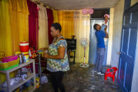 Verty plays with his 1-year-old daughter while his wife Saint Jean fixes the house in Port-au-Prince, Haiti, Tuesday, Aug. 25, 2020. The Trump administration has sharply increased its use of hotels to detain immigrant children before expelling them from the United States during the coronavirus pandemic. Verty says government contractors at a hotel where he was detained gave his family, including his daughter, cups of ice to eat to pass temperature checks prior to their deportation flight, even though they had tested negative for COVID-19. (AP Photo/Dieu Nalio Chery)