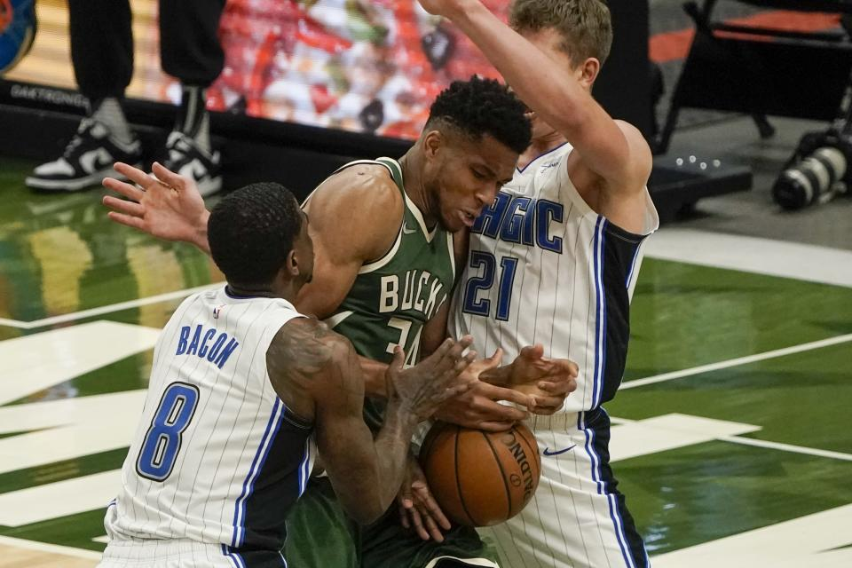 Milwaukee Bucks' Giannis Antetokounmpo battles for a loose ball with Orlando Magic's Dwayne Bacon and Moritz Wagner during the second half of an NBA basketball game Tuesday, May 11, 2021, in Milwaukee. (AP Photo/Morry Gash)