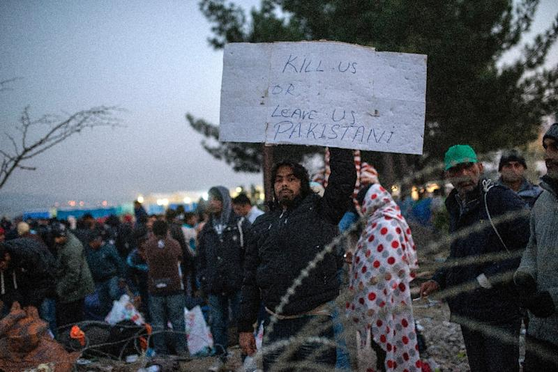 A migrant from Pakistan holds a placard as he waits with other migrants and refugees to cross the Greek-Macedonian border near Gevgelija on November 20, 2015 (AFP Photo/Robert Atanasovski)