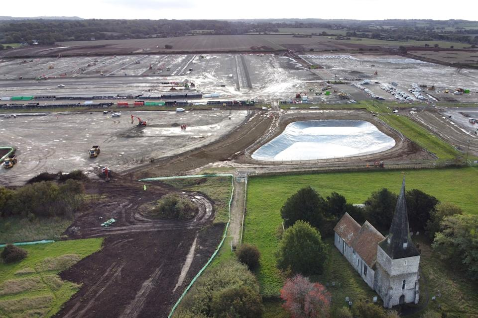 An aerial picture shows St Mary's Church in the foreground as construction continues at a site of a lorry park being built between the villages of Sevington and Mersham, near the M20 motorway near Ashford in Kent, south east England on October 6, 2020, which will have the capacity to hold nearly 10,000 vehicles in the event of a no-deal Brexit. - Queues of up to 7,000 heavy-goods vehicles could develop in southeast England from January if Britain leaves the European Union without a Brexit trading deal, the government forecast last month. In case of a no-deal Brexit, Britain's government is developing giant lorry parks in Kent to prevent gridlock on the road system leading in and out of London. (Photo by BEN STANSALL / AFP) (Photo by BEN STANSALL/AFP via Getty Images)