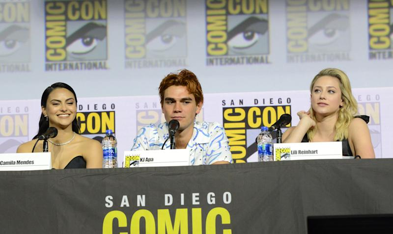 "SAN DIEGO, CALIFORNIA - JULY 21: (L-R) Camila Mendes, KJ Apa and Lili Reinhart speak at the ""Riverdale"" Special Video Presentation and Q&A during 2019 Comic-Con International at San Diego Convention Center on July 21, 2019 in San Diego, California. (Photo by Albert L. Ortega/Getty Images)"