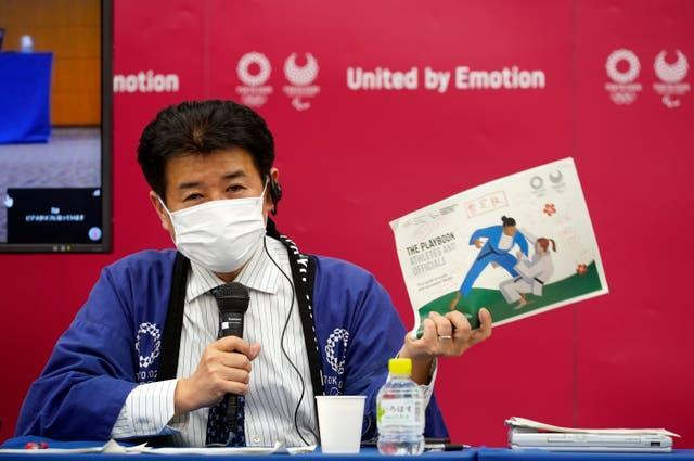 Tokyo 2020 Games delivery officer Hidemasa Nakamura holding a copy of the playbook during a media briefing on Wednesday