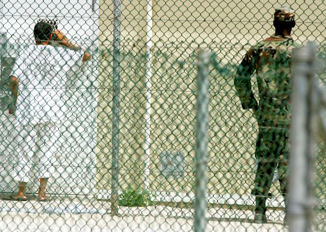 GUANTANAMO BAY, CUBA - AUGUST 26: A detainee looks into the window of a cell at Camp 4 inside of the maximum security prison Camp Delta at Guantanamo Naval Base August 26, 2004 in Guantanamo Bay, Cuba. This week the U.S. Military held preliminary hearings for four detainee's charged with conspiricy to commit war crimes. (Photo by Mark Wilson/Getty Images)