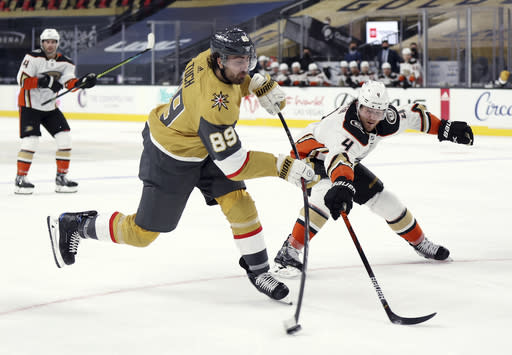 Vegas Golden Knights right wing Alex Tuch (89) shoots as Anaheim Ducks Cam Fowler (4) defends during the second period of an NHL hockey game Saturday, Jan. 16, 2021, in Las Vegas. (AP Photo/Isaac Brekken)