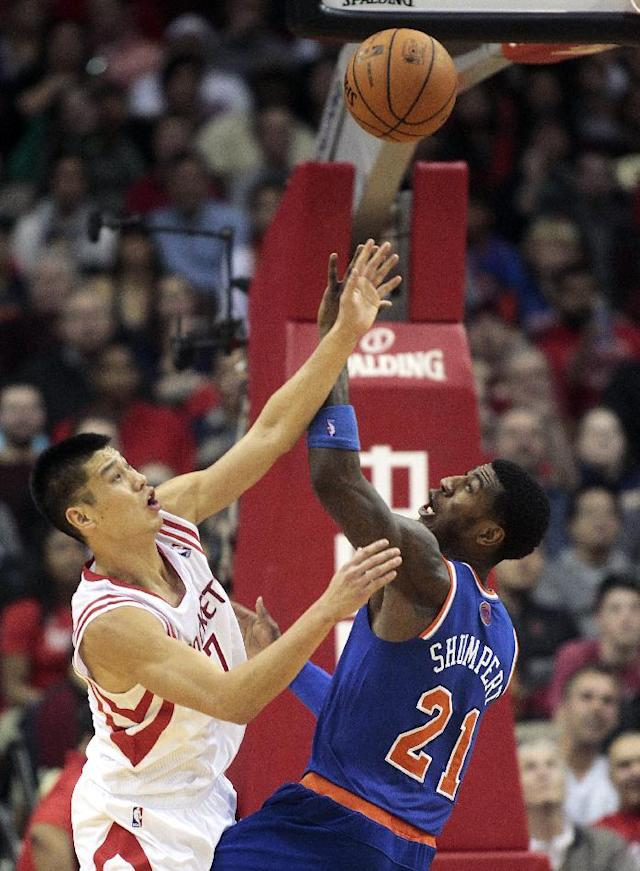 Houston Rockets guard Jeremy Lin (7) takes a shot over New York Knicks guard Iman Shumpert (21) during the second period of an NBA basketball game, Friday, Jan. 3, 2014, in Houston. (AP Photo/Patric Schneider)
