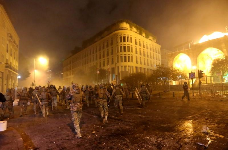 Smoke rises as Lebanese army soldiers walk during a protest against the newly formed government in Beirut