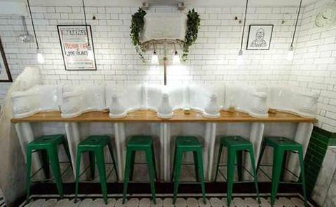 If it looks the stools are facing into urinals at the Attendant café in London, that's because they are. Photo: Leon Neal/AFP