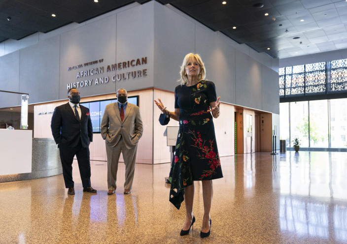 First lady Jill Biden speaks to gathered employees and media during a visit to the National Museum of African American History and Culture with Lonnie Bunch, Secretary of the Smithsonian, center, and National Museum of African American History and Culture director Kevin Young, left, Friday, May 14., 2021, in Washington. (AP Photo/Carolyn Kaster)