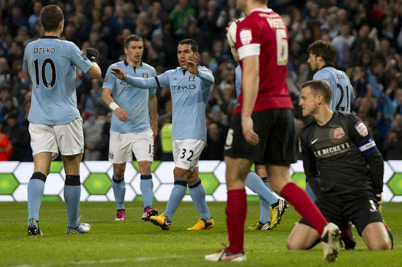 Manchester City's Carlos Tevez, centre, celebrates with teammates after scoring his second goal past Barnsley's goalkeeper Luke Steele, bottom right, during their English FA Cup quarterfinal soccer match at The City of Manchester Stadium, Manchester, England, Saturday, March 9, 2013. (AP Photo/Jon Super)