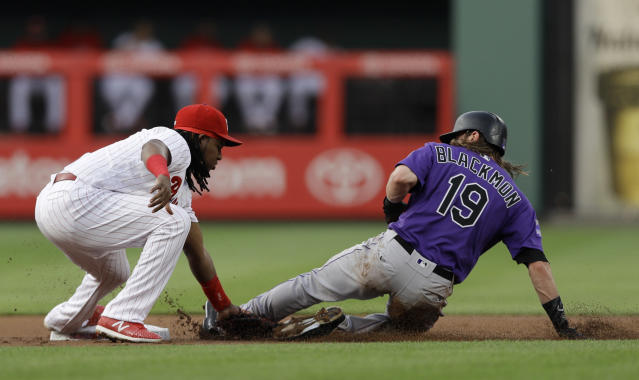Philadelphia Phillies third baseman Maikel Franco, left, tags out Colorado Rockies' Charlie Blackmon at second base after Blackmon tried to steal during the first inning of a baseball game, Wednesday, June 13, 2018, in Philadelphia. (AP Photo/Matt Slocum)