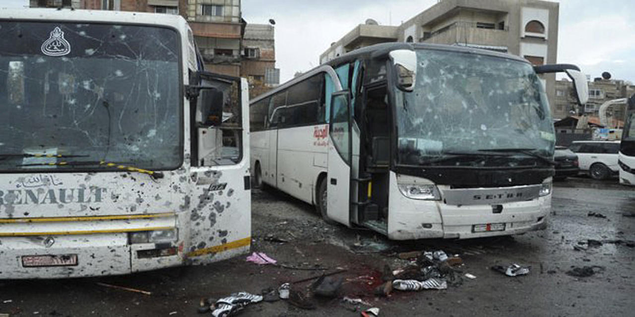 <p>This photo released by the Syrian official news agency SANA shows blood soaked streets and several damaged buses in a parking lot at the site of an attack by twin explosions in Damascus, Syria, Saturday, March 11, 2017. (SANA via AP) </p>