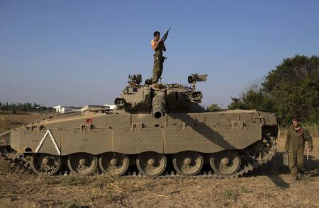 An Israeli soldier checks his weapon atop a tank near the border with Gaza