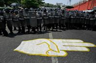 Riot police guard a road in Yangon Thursday in front of a street mural of a three-finger salute popular among anti-coup protesters
