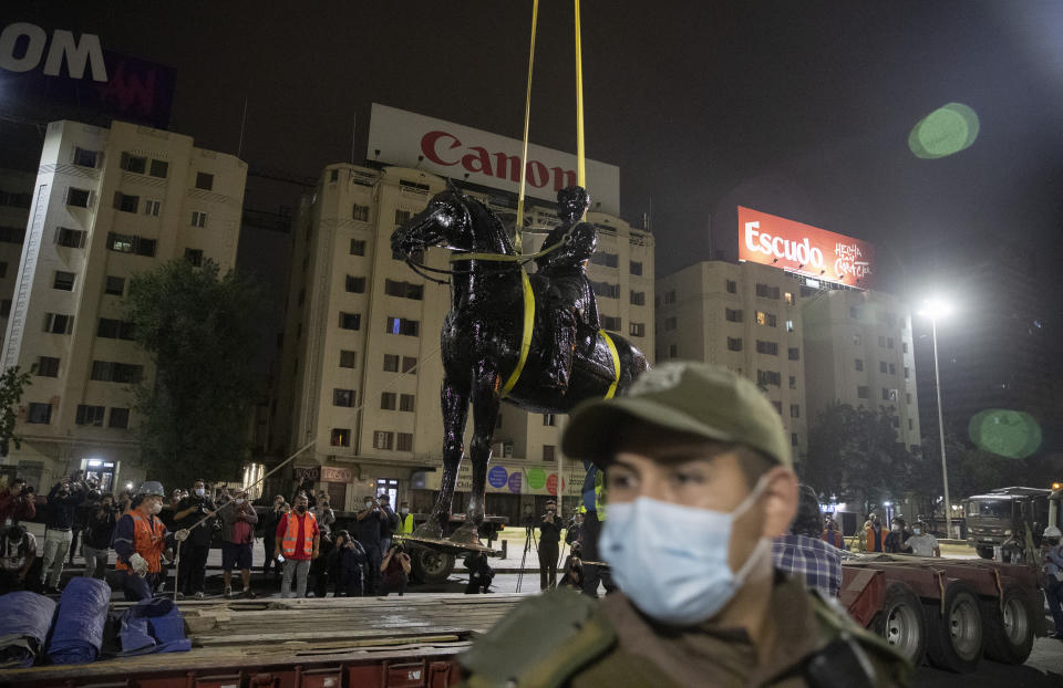 Cranes remove the statue of Gen. Manuel Baquedano, a Chilean military officer and politician, at Plaza Italia Friday, March 12, 2021, in Santiago, Chile. The statue located at the epicenter of the protests in Chile was removed early Friday be order of the National Monuments Council to be restored. (AP Photo/Esteban Felix)