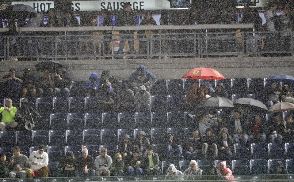 Fans endure rain during the seventh inning of a baseball game between the New York Yankees and the Kansas City Royals, Friday, April 19, 2019, in New York. (AP Photo/Frank Franklin II)