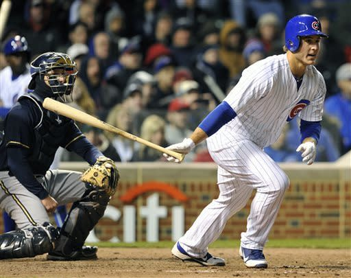 Chicago Cubs' Anthony Rizzo watches his RBI double, in front of Milwaukee Brewers catcher Jonathan Lucroy during the seventh inning of a baseball game Tuesday, April 9, 2013, in Chicago. (AP Photo/Jim Prisching)