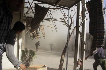 Smoke rises as people run at a site hit by shelling in Arbeen