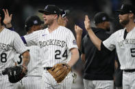 Colorado Rockies third baseman Ryan McMahon (24) and teammates congratulate one another after an 8-4 win over the San Diego Padres in a baseball game Tuesday, June 15, 2021, in Denver. (AP Photo/David Zalubowski)