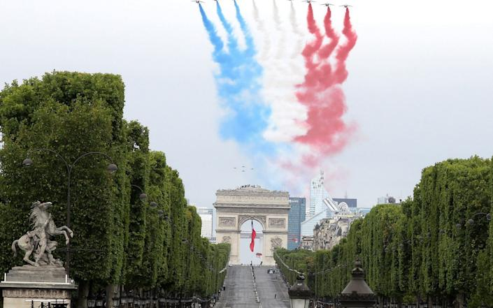 """French elite acrobatic flying team """"Patrouille de France"""" (PAF) performs a flying display of the French national flag over the Arc de Triomphe during annual Bastille Day military ceremony on the Place de la Concorde in Paris - Ludovic Marin/AFP"""