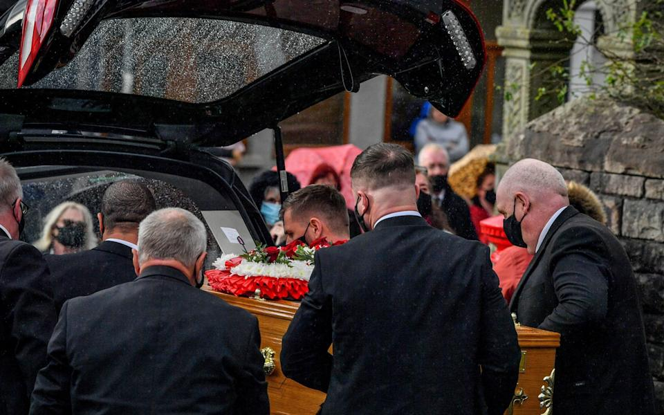 The coffin of Gladys Lewis is placed into the hearse during the funeral  - PA