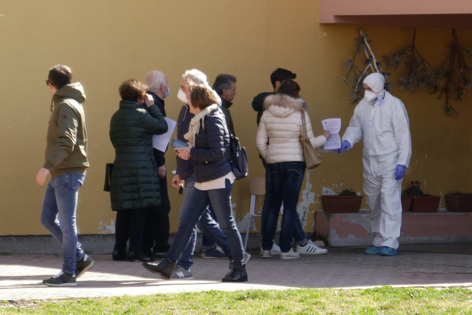 People line up to undergo a voluntary test of Coronavirus, part of a study of the University of Padua, in Vo' Euganeo, a town of 3,500 people at the epicenter of the Veneto cluster, which was sealed off until Sunday, March 8, 2020. Italy announced a sweeping quarantine early Sunday for its northern regions, igniting travel chaos as it restricted the movements of a quarter of its population in a bid to halt the new coronavirus' relentless march across Europe. (AP Photo/Andrea Casalis)