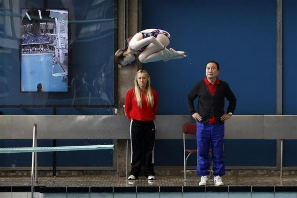 A member of Crystal Palace diving club dives watched by head coach Chen Wen (R) during a training session in London March 9, 2012.