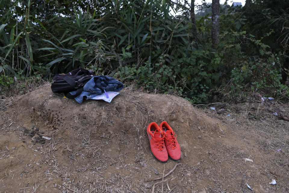 A pair of football boots lie next to a change of clothes by the side of a football field where a friendly match is in progress, in Shangshak village, in the northeastern Indian state of Manipur, Saturday, Jan. 30 2021. Most young boys play soccer in these Tangkhul Naga villages. And when matches are played, the village turns up to show support - the elderly squinting, parents carrying infants, young boys making bonfires to keep spectators warm. (AP Photo/Yirmiyan Arthur)