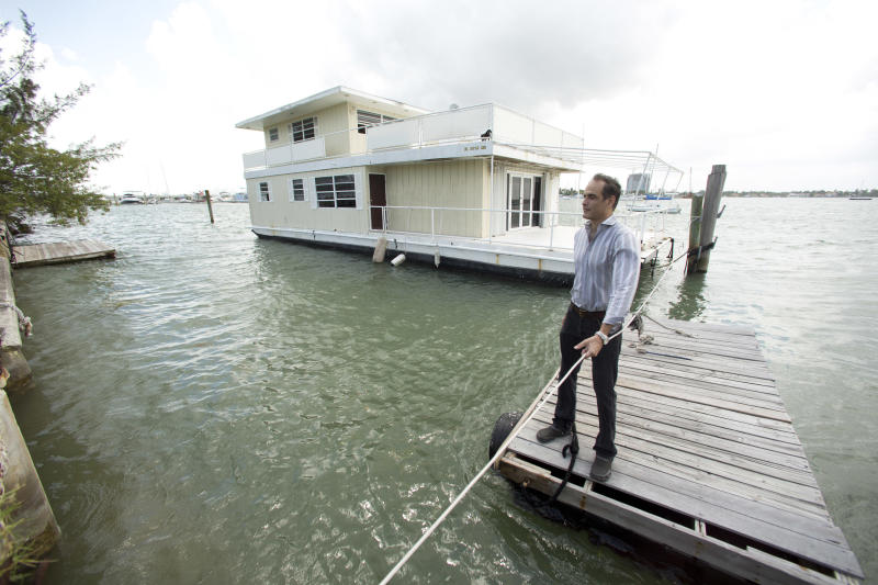 In this April 22, 2014 photo, Fane Lozman pulls his dock away from his home floating in the waters near North Bay Village, Fla., as he returns to the shoreline. Lozman caught legal lightning in a bottle last year when the U.S. Supreme Court agreed with him that his floating home was a house, not a vessel covered by maritime law. But the justices haven't had the last word: Lozman is still fighting for compensation for the home, which was destroyed years ago. The Fort Lauderdale-based federal judge whose decision on the floating home was overturned, U.S. District Judge William Dimitrouleas, refused earlier this year to give Lozman any of the $25,000 bond posted by the city of Riviera Beach to pay for Lozman's home in case he won. (AP Photo/J Pat Carter)