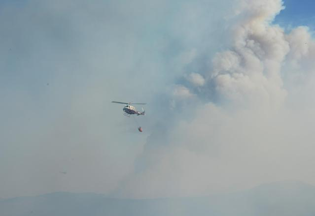 NEWBURY PARK, CA - MAY 02: A fire fighting helicopter prepares for a water drop onto an out of control wildfire on May 2, 2013 in Newbury Park, California. Hundreds of firefighters are battling wind and dry conditions as over 6000 acres have already been burned northwest of Los Angeles. (Photo by Kevork Djansezian/Getty Images)