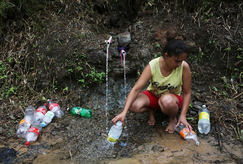 Yanira Rios collects spring water for use in her house last week in Utuado, Puerto Rico. Most of the municipality has been without running water or electricity since Hurricane Maria hit the island on Sept. 20.