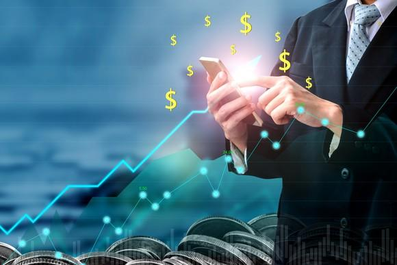 Businessman holding cell phone with line chart going up and dollar signs in foreground
