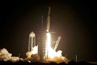 FILE PHOTO: A SpaceX Falcon 9 rocket, with the Crew Dragon capsule, is launched carrying four astronauts on a NASA commercial crew mission