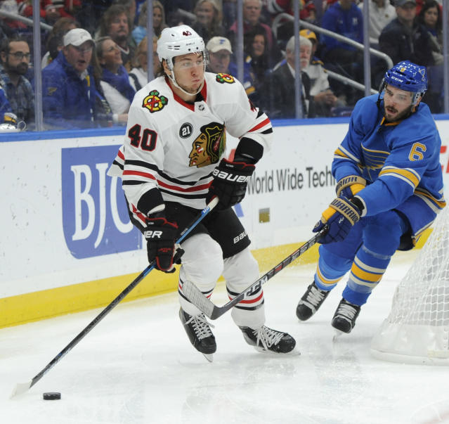 Chicago Blackhawks' John Hayden (40) skates by St. Louis Blues' Joel Edmundson (6) during the first period of an NHL hockey game, Saturday, Oct. 27, 2018, in St. Louis. (AP Photo/Bill Boyce)