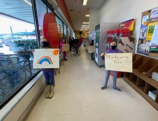 Club members spread smiles through positive signs and by paying for portions of peoples' groceries at a local store in Whitehorse.