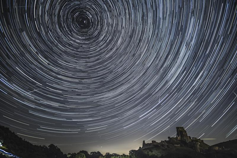 Comets streak across the night sky beneath stars that appear to rotate in a long-exposure photograph taken above Corfe Castle, Dorset on August 12, 2016: Getty Images